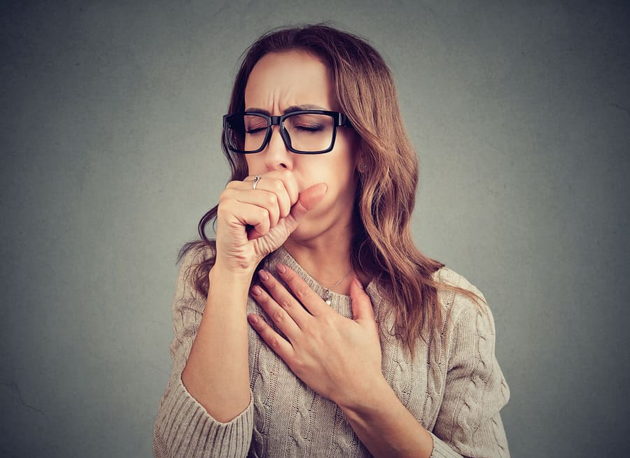 a young woman experiencing a chronic cough due to mold exposure